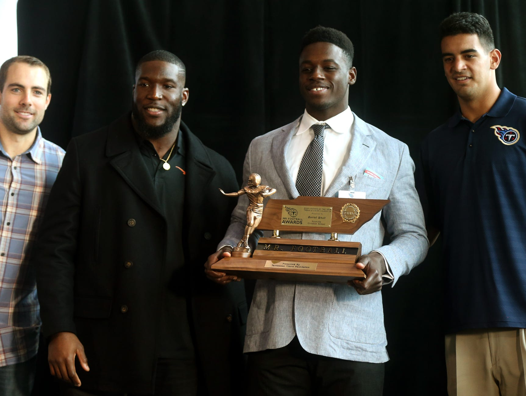 Nashville Christian's Daniel Bituli holds his Class 1A Mr Football Lineman award with Titans players (L to R) Ryan Succop, Brian Orakpo and Marcus Mariota Monday.