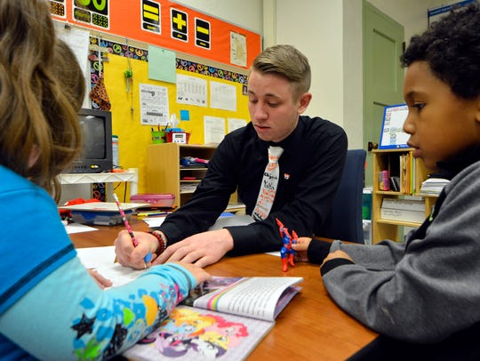 Student teacher Brian Baker works with students Bella