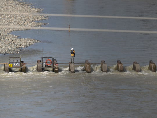 Workers repair a section of the ACID diversion dam