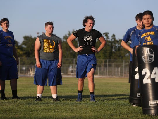 Anderson High School senior Jarrett Kingston, center, talks with teammates during football practice in September. On Wednesday, Kingston signed to play as an offensive lineman for the Washington State Cougars.