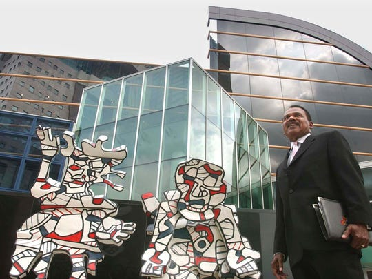 "Ken Clay, former Kentucky Center for the Arts programming director, standing next to the ""Faribolus and Perceval"" artwork."