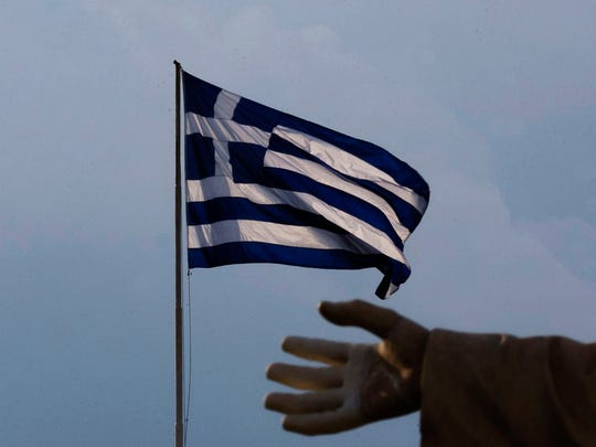 A hand of a statue is seen as the Greek flag waves