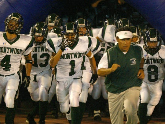11/05/2003: Members of the Montwood High School football team, led by head coach Chuck Veliz, take the field.