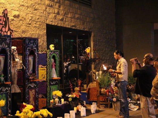A man burns incense in front of a community altar during the Arizona Latino Arts & Culture Center's (ALAC) Dia de los Muertos festival.