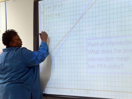 Lisa Himes, an algebra and geometry teach at Northwood High School, works a math problem during Eureka Math Night Thursday Dec. 17, 2014.