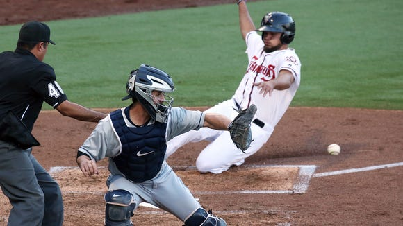 El Paso Chihuahuas first baseman Diego Goris slides safely into home plate while Tacoma Rainiers catcher Tuffy Gosewisch moves to catch the throw from the outfield Tuesday night at Southwest University Park.