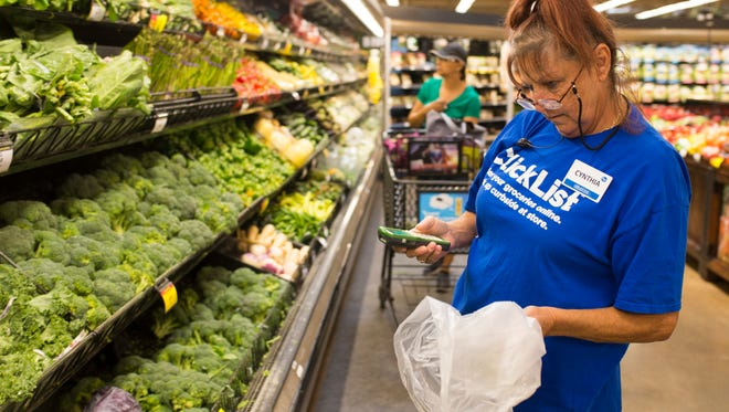 Cynthia Laing works on fulfilling a ClickList customer order in the produce section at the Shelbyville Road Kroger location. ClickList employees are trained on how to select the best produce in stock for customers. July 25, 2017