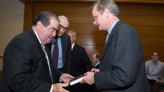 Lawrence Lessig gives Justice Antonin Scalia a book in 2014.