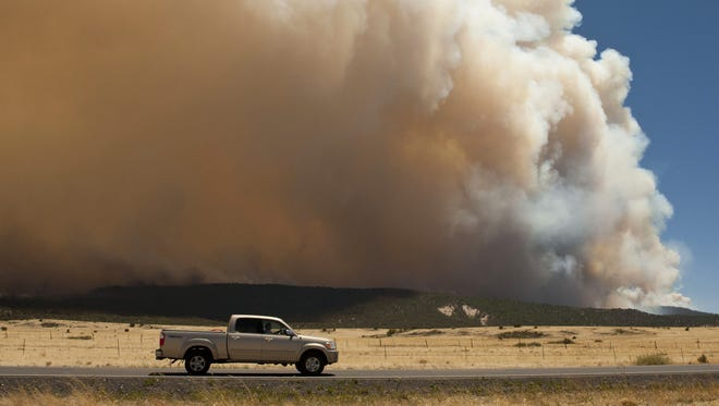 A truck drove west on Highway 260 away from the Wallow fire as it burns to about 1 mile from the western edge of Eagar.