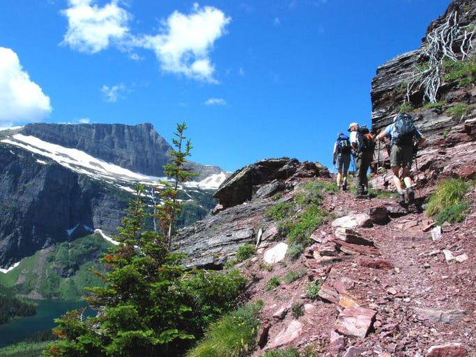 Hikers climbing to Triple Divide Pass look down on Medicine Grizzly Lake.