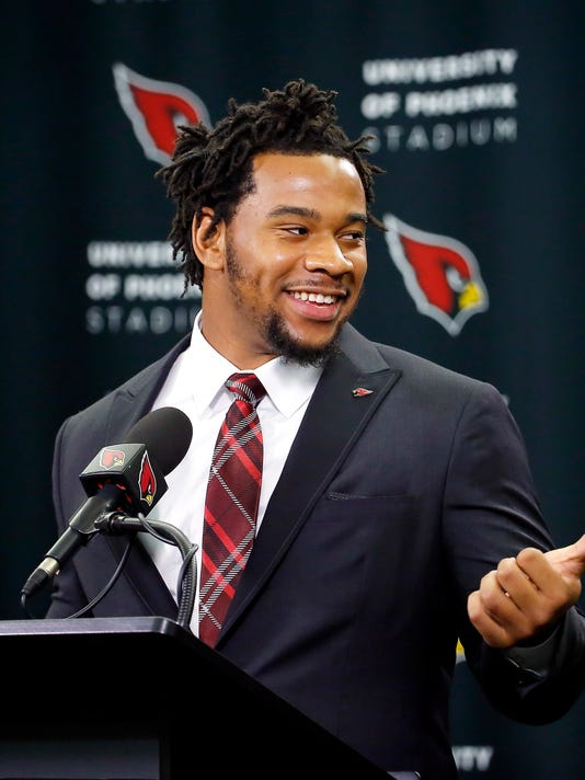 Arizona Cardinals' first-round draft pick Robert Nkemdiche points to head coach Bruce Arians after being introduced to the media, Friday, April 29, 2016, in Tempe, Ariz. Nkemdiche was the Cardinals' first round, 29th overall, pick in the NFL football draft. (AP Photo/Matt York)
