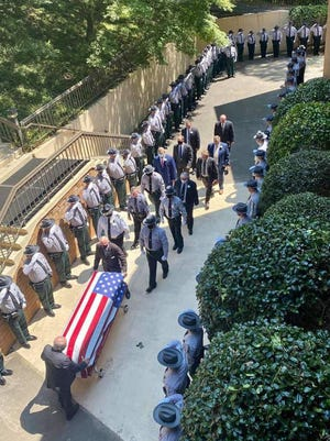 Law enforcement officers line a walkway at the Georgia Baptist Conference Center as the casket of DNR Capt. Stan Elrod is carried at his funeral Tuesday in Stephens County.