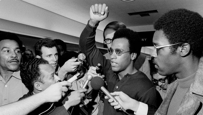 Huey Newton, Black Panther Party minister of defense, raises his arm as he is literally surrounded by the press at Philadelphia's International Airport, Sept. 4, 1970 upon his arrival for a three-day convention in Philadelphia.