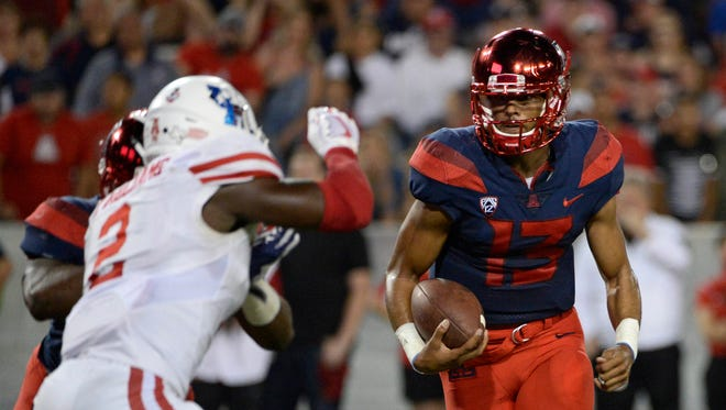 Arizona Wildcats quarterback Brandon Dawkins (13) runs the ball under pressure from Houston Cougars safety Khalil Williams (2) during the second half at Arizona Stadium.