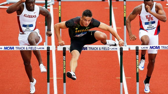 Oregon's Devon Allen, center, clears a hurdle on his way to winning a semifinal in the men's 110-meter hurdles, between Alabama's Tony Brown, left, and Houston's Isaac Williams at the NCAA outdoor track and field championships in Eugene, Ore., Wednesday, June 8, 2016. (AP Photo/Ryan Kang)