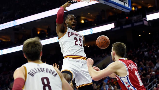 Cleveland Cavaliers' LeBron James (23) dunks the ball over Philadelphia 76ers' Nik Stauskas during the second half of Monday's game in Philadelphia. The Cavaliers won, 107-100.