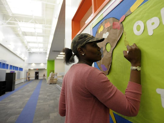 Azilee Kent, an art teacher, decorates a wall in a corridor at Willow Charter Academy in Lafayette last year.