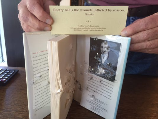 Chan Gordon Holds A Copy Of The Billy Collins Poetry Book Discovered At Captains Bookshelf Signed First Edition Had Been Blasted With 410 Gauge