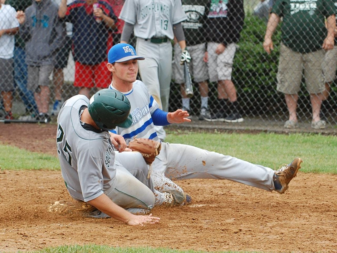 Nick Polizzano of South Plainfield is safe at the plate as Northern Burlington pitcher Ryan Shinn applies a late tag in the fifth inning Saturday.