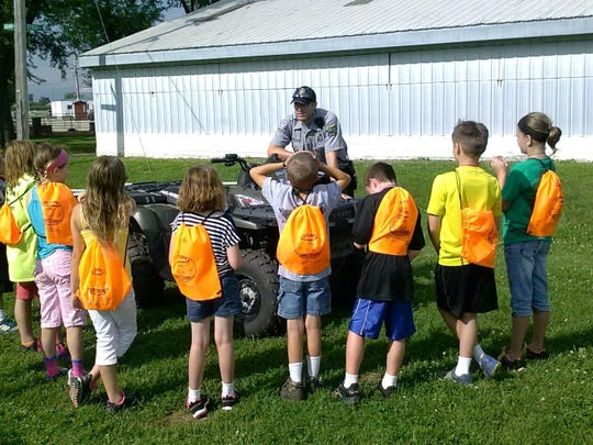Youth chat with an officer about police equipment during