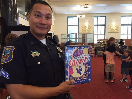 """Wilmington police Senior Cpl. Isreal Santiago shows the book he read to young guests at Wilmington Library's summer reading program, """"Officer Buckle and Gloria,"""" by Peggy Rathman, about a policeman and his canine partner who share safety tips and the story of their partnership with visits to schools."""