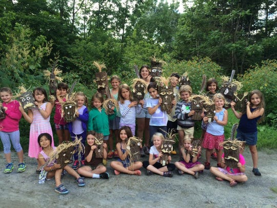 Campers show their goofy, funny and spooky masks made from bark and natural materials at the Art from Nature Camp at Poker Hill Arts in Underhill.