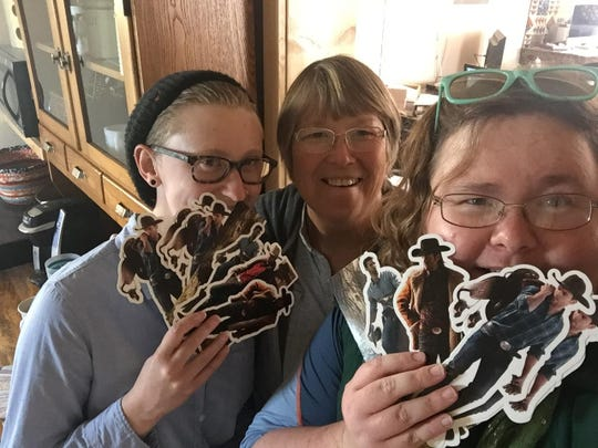 """Tribune Photographer Julia Moss, Malta romance novelist B.J. Daniels and Tribune Montana Mystique Writer Kristen Inbody pose with """"Flat Cowboy"""" bookmarks in her Malta office, one of Moss and Inbody's many detours. The """"Flat Cowboy"""" bookmarks traveled with the duo to Montana's four corners and posed for photos all over the state."""