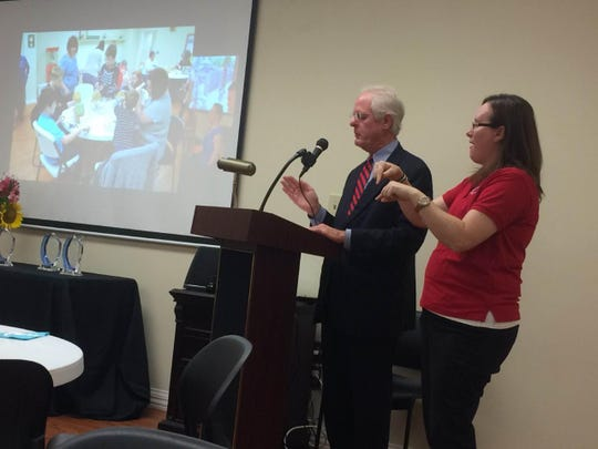JCIL Board Treasurer Bart Smith and a translator communicate at a celebration of the anniversary of the signing of the Americans with Disabilities Act.