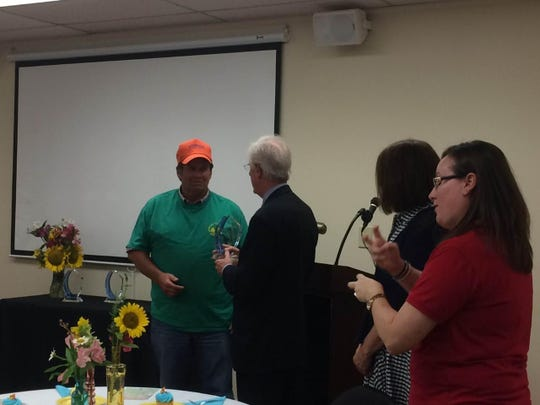 JCIL Board Treasurer Bart Smith presents the Volunteer Group of the Year Award to the Baptist Builders.