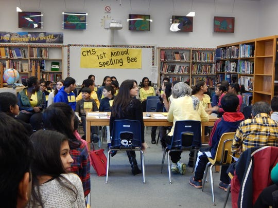 Contestants and audience members sit in the library awaiting the start of Central Middle School's First Spelling Bee.