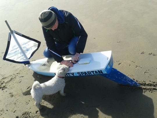 Sean Creavan and his dog, Daisy, inspect The Mighty Spartan boat on Strandhill Beach in County Sligo, Ireland. The boat was designed by students at Lake Forest Central Elementary school and launched off the Atlantic Ocean and washed up in Ireland.
