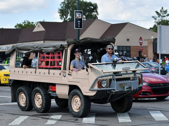 Some type of possibly military or amphibious vehicle cruises south during the Woodward Dream Cruise on Woodward Avenue in Birmingham, Mich. on Aug. 19, 2017. 