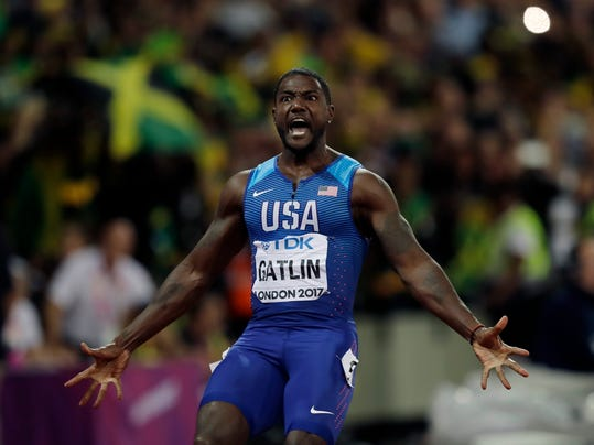 """FILE - In this Aug. 5, 2017 file photo, United States' Justin Gatlin celebrates after crossing the line to win the gold medal in the men's 100m final during the World Athletics Championships in London. World sprint champion Gatlin says he won't be taking the knee in protest this weekend at an exhibition race in Brazil. Asked about it before Sunday's race, Gatlin says, """"I'm going to stand up. I mean, I'm going to stand up. I'm not saying if I take the knee or stand, I'm not for the protests."""" (AP Photo/Tim Ireland, File)"""