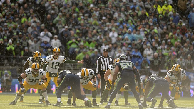 Green Bay Packers quarterback Aaron Rodgers (12) gives orders to his players at the line of scrimmage during the NFC Championship game against the Seattle Seahawks at CenturyLink Field.