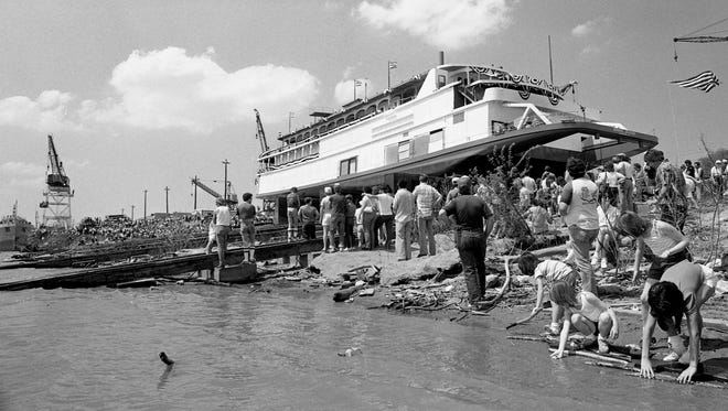 With kids playing at the edge of the Ohio River, some of the spectators get a closer look at Opryland new General Jackson showboat before it launch from the Jeffboat Co. work site in Jeffersonville, Ind. April 20, 1985.