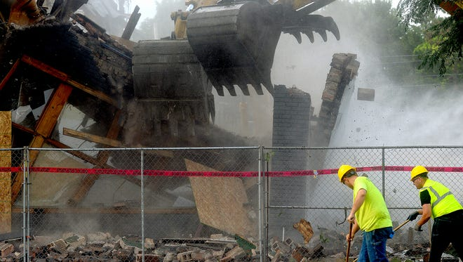 Crews from SC Services Environmental start the demolition of most of the 2000 block of Michigan Avenue Monday, July 25, 2016, in Lansing. Developer Scott Gillespie is tearing down the buildings, including Emil's Italian restaurant, to make way for his $5 million mixed-use development called East Town Flats.