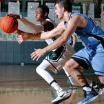 Williamston's Seth Kerby, left, and Lansing Catholic's Michael Korrey battle for control of the ball Friday, Feb. 27, 2015, in Williamston, Mich. Williamston won 65-58.