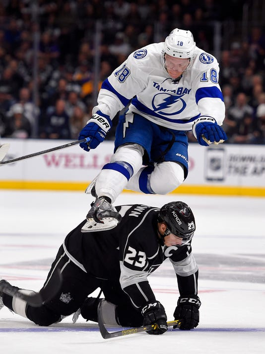 Tampa Bay Lightning left wing Ondrej Palat, top, of the Czech Republic, jumps over Los Angeles Kings right wing Dustin Brown during the third period of an NHL hockey game, Monday, Feb. 16, 2015, in Los Angeles.  The Kings won 3-2. (AP Photo/Mark J. Terrill)