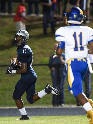 Powdersville junior Tay Cureton (13) looks back toward Wren senior Tyrese Franklin (11) while scoring a touchdown against Wren during the first quarter at Powdersville High School on Friday.