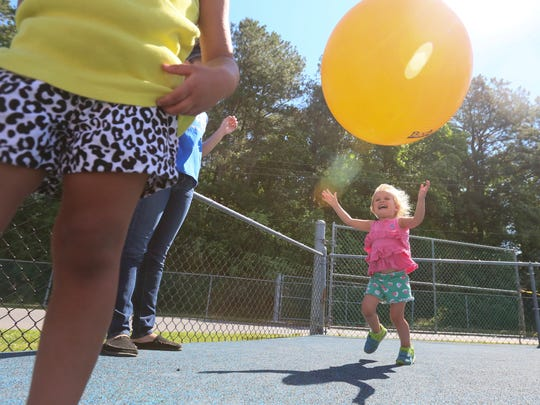 Two-year-old Laine Hade, a toddler in the Parents and Children Together at Tech United Cerebral Palsy of Delaware child care center at Sussex Technical High School, plays with a ball on the playground Wednesday morning.