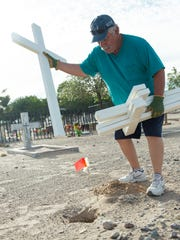 Jose Tapia, with the Knights of Columbus, joins with St. Genevieve Catholic Church Historical Society to install 49 crosses at San Jose Cemetery on Monday, May 28, 2018. The crosses were made by Stephen Elchlepp, with Tonto Basin Fort Reno VFW post 8807.
