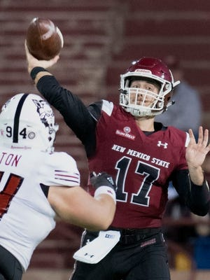 Aggies quarterback Tyler Rogers passes deep over Arkansas State's Hunter Moreton during second quarter action Saturday night at Aggie Memorial Stadium. 10/28/17  Gary Mook/ for the Sun-News