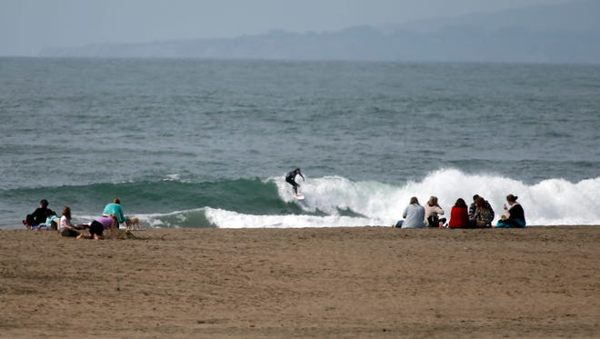 Beach goers and surfers enjoy the warm weather at Ocean Beach in San Francisco. California and the San Francisco Bay Area are experiencing their warmest winter weather on record.