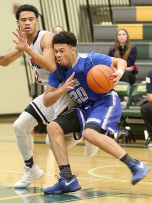 Olympic's Jaiden Mosley (right) struggles to drive the lane against Lindbergh's defense in Friday's Class 2A West Central District game at Foss High in Tacoma. Lindbergh won, 62-54.
