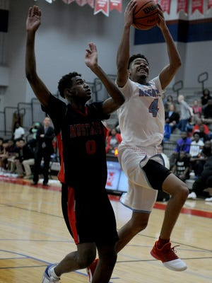 Hirschi's Javen Banks drives to the basket next to Waxahachie Life's Justin Nimmer Tuesday, Feb. 28, 2017, in the Region I-4A Regional Quarterfinals at Northwest High School in Justin. The Mustangs defeated the Huskies 42-24.