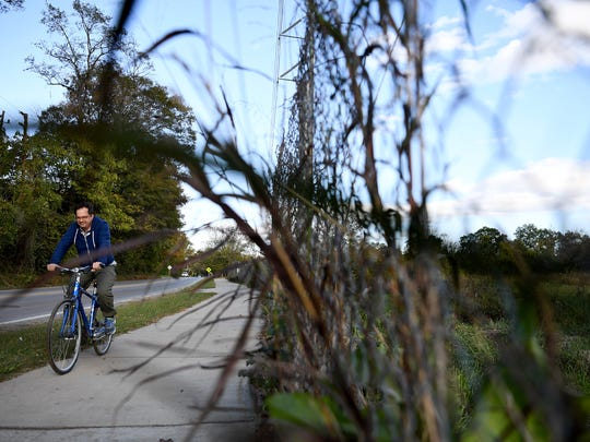 A man rides a bicycle on the sidewalk next to Amboy Road along the French Broad River Greenway next to the fence surrounding the Karen Cragnolin River Park on Wednesday, Oct. 25, 2017. After years of trying to remove contaminants from the soil, RiverLink has formed a committee to start to design the park.