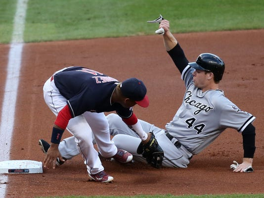 Cleveland Indians' Jose Ramirez is late on the tag as Chicago White Sox's Justin Morneau slides into third base safe after tagging on a fly out by Todd Frazier during the first inning of a baseball game Thursday, Aug. 18, 2016, in Cleveland. (AP Photo/Aaron Josefczyk)