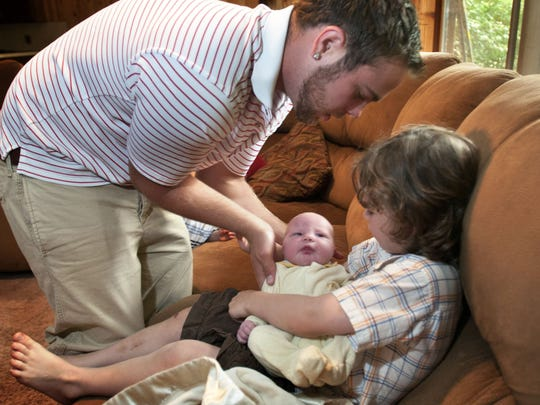 In this Aug. 6, 2013, photo, Tyler Schwandt, left, shows younger brother Wesley how to support newborn Tucker's head in their home in Rockford, Mich. Jay and Kateri Schwandt have 12 children.