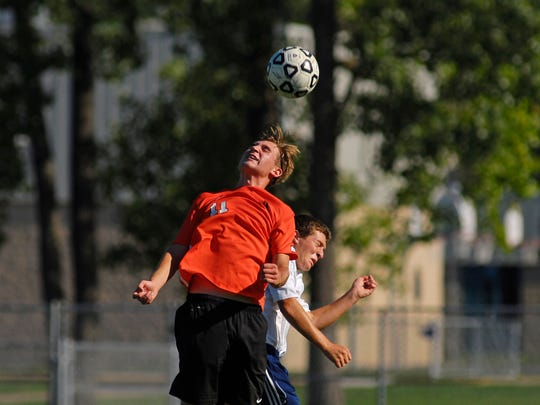 Nate Miller of Almont goes up for a header against Richmonds' Robert Trombley Monday, Aug. 30, during a varsity soccer match at Richmond.