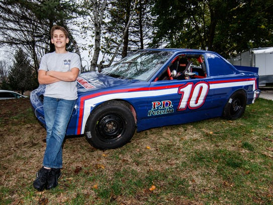 Ricky Gebhard, 13, with his race car on Monday, Oct.